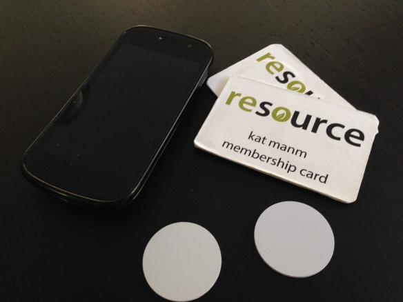 A phone, two mock-up membership cards with RFID tags embedded, and two raw RFID tags